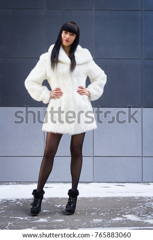 Beauty fashion model girl in a white mink fur coat posing on a city street. Beautiful Luxury Winter Woman. Sexy asian girl in fur coat #765883060