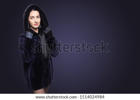 Beauty Fashion Model Girl in Blue Mouton Fur Coat. Beautiful Luxury Winter Woman in short coat with hood on blue background with copy space. #1514024984
