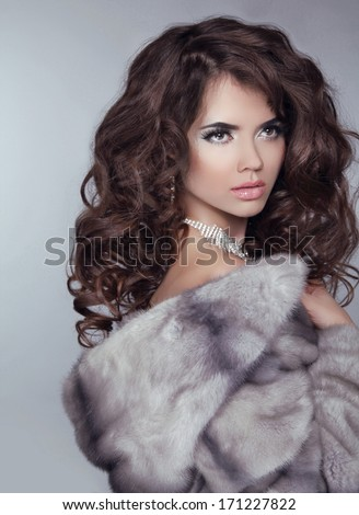 Beauty Fashion Model Girl in Mink Fur Coat. Beautiful Luxury Winter Woman isolated on gray background