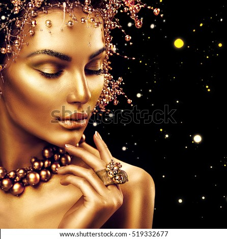 Beauty Fashion model girl with Golden Makeup, Gold skin makeup, hair and jewellery on black background. Gold earrings, ring and necklace. Metallic, glance Fashion art portrait, Hairstyle, make up