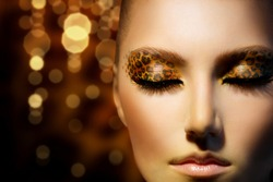 Beauty Fashion Model Girl with Holiday Leopard Makeup. Golden Wild Cat Eyes Make-up Eyeshadow. Beautiful Woman Face with Perfect skin. Animal Make up