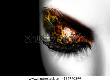 Beauty Fashion Model Girl with Holiday Leopard Makeup. Golden Wild Cat Eyes Make-up Eyeshadow. Beautiful Woman Face with Perfect skin. Animal Make up. Black and White Portrait closeup