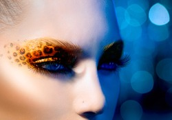 Beauty Fashion Model Girl with Holiday Leopard Makeup. Yellow Wild Cat Eyes Make-up Eyeshadow. Beautiful Woman Face with Perfect skin. Animal Make up. Blue Abstract Bokeh Background