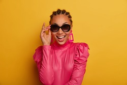 Beauty fashion model keeps hand on sunglasses, smiles positively, dressed in pink stylish clothes, being in good mood, rejoices buying new outfit, poses against yellow background. People and style