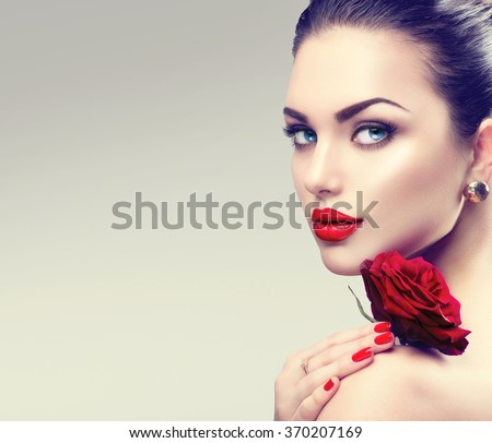Beauty Fashion Model Woman face. Portrait with Red Rose flower. Red Lips and Nails. Beautiful Brunette Woman with Luxury Makeup and Manicure.