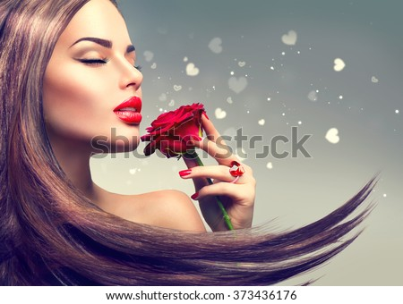 Beauty Fashion Model Woman with red rose flower. Red Lips and Nails. Valentine\'s Day Beautiful Fashion sexy Girl with flying long hair. Beautiful Sexy Brunette with Luxury Makeup and Manicure