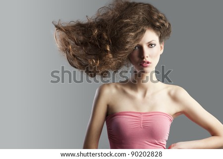 beauty fashion portrait of beautiful young brunette with curly hair flying and creative hairstyle. she looks in to the lens, has hair raised on the right and left hands on left hip.