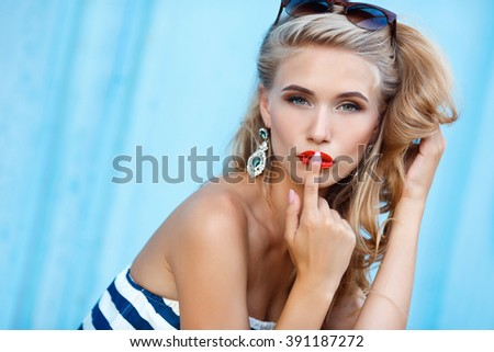 Stock Photo beauty fashion portrait of blonde woman with red lips and stripped dress. Fashion portrait. Smiling blonde woman in fashionable look. Sea style. On blue background. Style and hot girl outdoor.