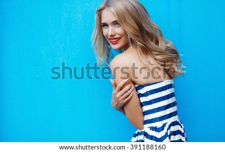 beauty fashion portrait of blonde woman with red lips and stripped dress. Fashion portrait. Smiling blonde woman in fashionable look. Sea style. On blue background. Style and hot girl outdoor.