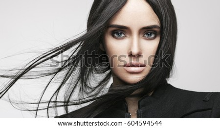 Beauty fashion portrait of young beautiful brunette girl with long black straight flying hair. Magnificent hair. Smoky eyes. Vogue style.