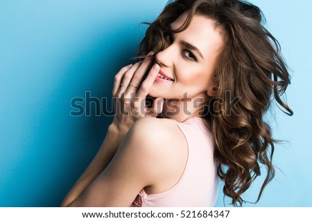 Beauty fashion portrait. Smiling young woman on blue wall background.