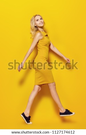 Beauty, fashion shot. Beautiful girl with a charming smile in a yellow dress on a yellow background. Full length portrait. #1127174612