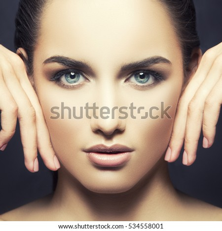 Stock Photo Beauty fashion vogue style face of caucasian brunette with elegant make-up, blue eyes, natural lips touching perfect skin. Close-up studio portrait isolated. Black background with grey spot. Toned