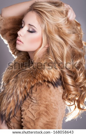 Beauty fashion woman in fur coat winter. Winter Girl in Luxury Fur Coat and evening makeup. Jewelry and Fashion elegant lady. Blond woman with long curly healthy hair. Studio.