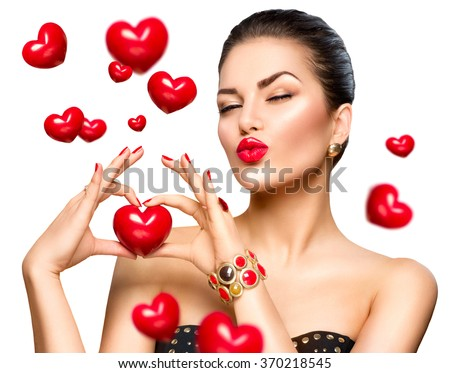 Stock Photo Beauty Fashion Woman showing red heart in her hand. Love concept, Valentine's Day. Beautiful model girl winking and kissing. Isolated on a white background