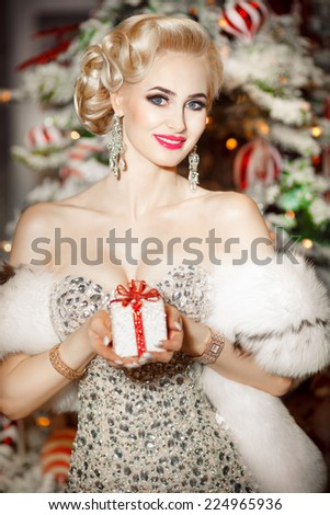Beauty fashion woman with Christmas gift box, new year tree background. Vogue style sexy girl. Gorgeous girl in luxury fur at Xmas party. Luxury life concept. Retro style girl makeup and jewelry model