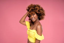 Beauty female colorful portrait of happy smiling attractive afro woman with curly hairstyle and glamour summer makeup. Pink pastel studio background. A lot of copy space.