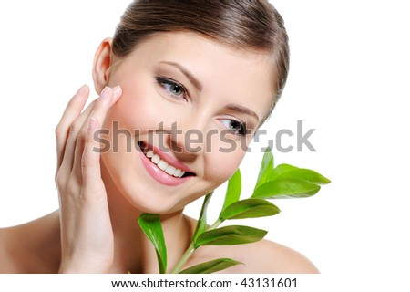 Beauty  female face with a clean purity skin touching cheek by her index finger