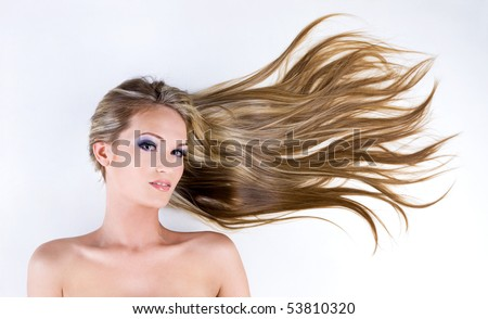Beauty female face with long blond straight hair and bright blue make-up