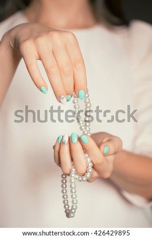Beauty female fingernails with turquoise and white french diamond manicure and pearl #426429895