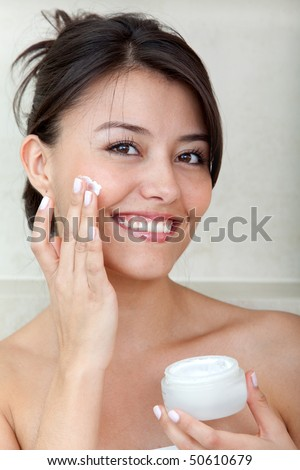 Beauty female portrait putting cream on her face