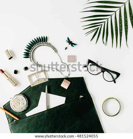 beauty feminine accessories arrangement with palm branch, purse, glasses, lipstick and necklace. flat lay, top view