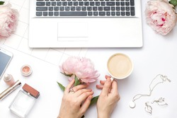 Beauty flat lay with a laptop and flowers. Woman's hands hold a peony and a cup of coffee. Top view composition.