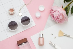 Beauty flat lay with cosmetic bottles, phone and flower. Top view