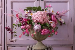 Beauty fresh bouquet of many different pink color flowers in old aged weathered metal flowerpot, planter,  scene in garden, vintage style, daylight