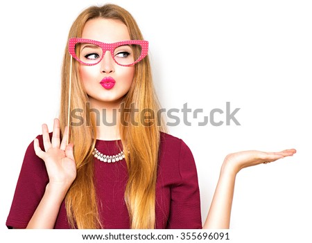 Shutterstock Beauty funny teenage girl with paper glasses on stick showing empty copy space on the open hand palm for text, white background. Happy girl presenting point. Proposing product. Advertisement gesture