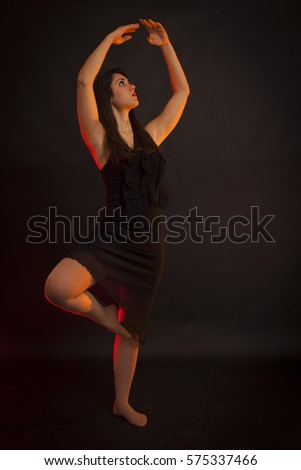 Beauty girl dancing in a dark room. black background, red backlight