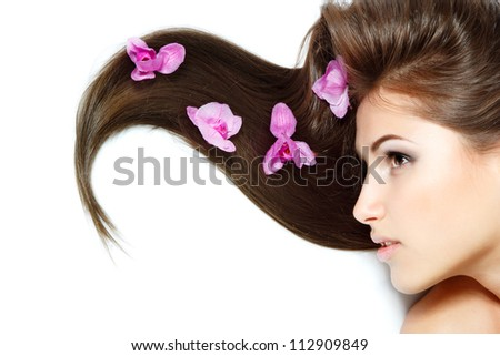 beauty girl, happy young natural beautiful woman over white background with long brown hair and purple orchid, over white background