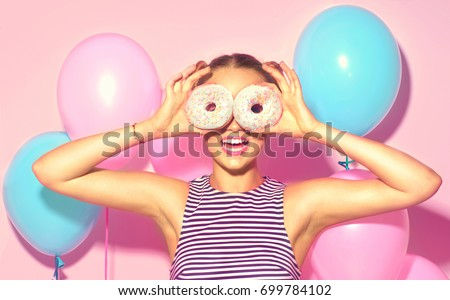 Beauty girl holding donuts and colorful air balloons laughing over pink background. Beautiful Happy Young woman on birthday holiday party with doughnuts. Joyful model Celebrating