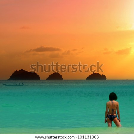 Beauty girl in bikini at the sea is standing knee-deep in water on sunset background. - stock photo