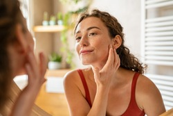 Beauty girl looking at mirror while touching her face and checking pimple, wrinkles and bags under the eyes, during morning beauty routine. Happy smiling beautiful young woman applying moisturizer.