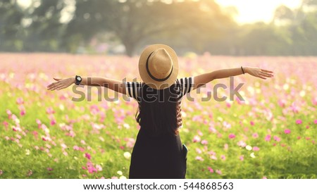 Beauty Girl Outdoors enjoying nature. Beautiful Teenage Model girl in black dress standing  on the Spring Field, Sun Light. freedom concept #544868563