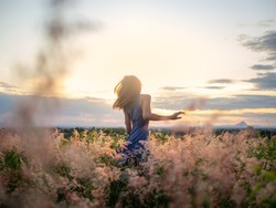 Beauty Girl Outdoors enjoying nature. Beautiful Teenage Model girl in the Spring Field, Sun shine.