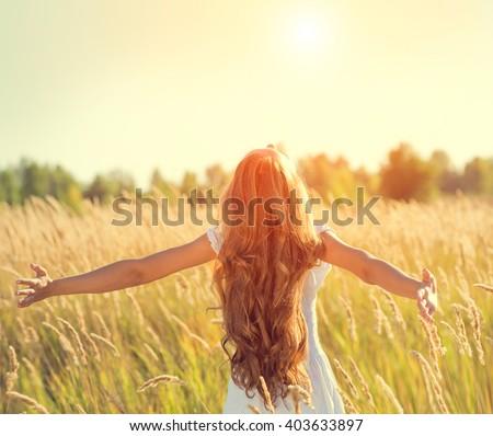 Beauty Girl Outdoors enjoying nature. Beautiful Teenage Model girl in white dress running on the Spring Field, Raising hands in Sun Light.