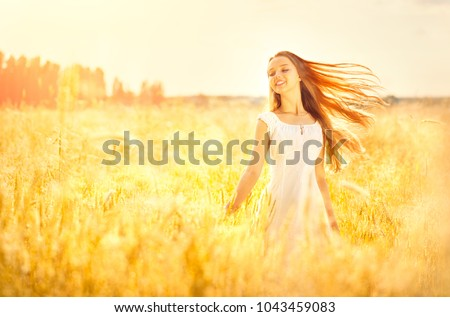 Beauty Girl Outdoors enjoying nature. Beautiful Teenage Model girl with healthy long hair, in white dress standing on the Spring Field, Raising hands in Sun Light