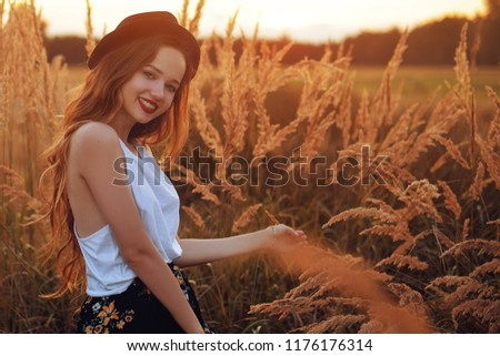 Beauty Girl Outdoors enjoying nature. Pretty Teenage Model in hat running on the Spring Field, Sun Light.  Romantic young blonde girl in a wheat field. Blowing Long Hair. Happy girl smile, sunset.