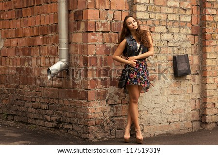 beauty girl posing fashion near red brick wall on the street