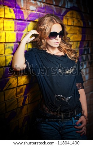 beauty girl posing fashion near red brick wall on the street .Young woman with sun glasses against a graffiti wall