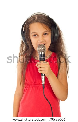 Beauty girl singing  into microphone and listening in headphones isolated on white background