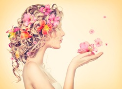 Beauty girl takes beautiful flowers in her hands. Blowing flower. Hairstyle with flowers.  Fantasy girl portrait in pastel colors. Summer fairy portrait. Long permed hair.