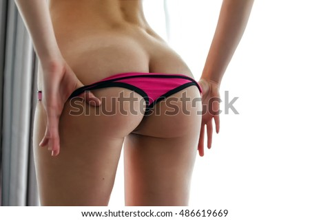Beauty girl takes off thong panties, showing sexy ass. Back view, Big window on the background.