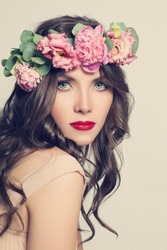Beauty Girl with Flowers Hairstyle. Beautiful Young Woman Portrait with Summer Pink  Peony Flowers. Long Permed Curly Hair and Fashion Makeup