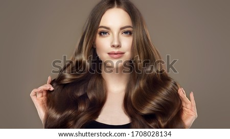 Photo of  Beauty girl with long  and   shiny wavy hair .  Beautiful   woman model with curly hairstyle .
