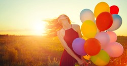 Beauty girl with long red hair holding colorful air balloons over sunset. Happy young healthy woman enjoying nature outdoors. Spinning romantic female with flying hair. Sunshine. Sunlight.