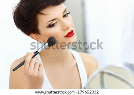 Shutterstock Beauty Girl with Makeup Brush. Natural Make-up for Brunette Woman with Red Lips. Beautiful Face. Applying Makeup