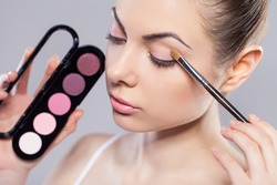 Beauty girl with makeup brushes. Perfect smooth skin.Applying makeup. Application of shadows on the model's eyes.
